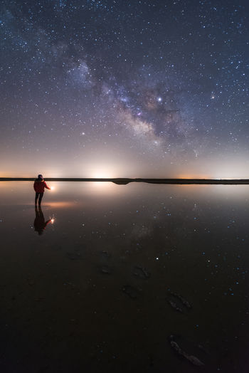 Man holding sparkler standing on beach against sky at night