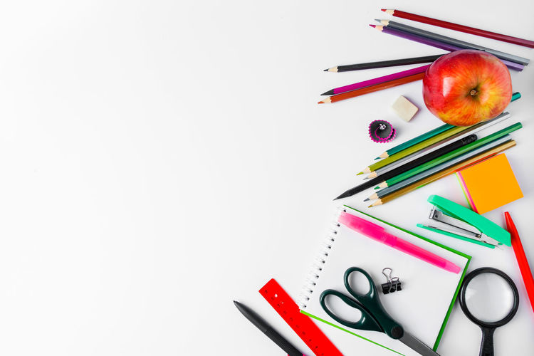 High angle view of colored pencils on table against white background