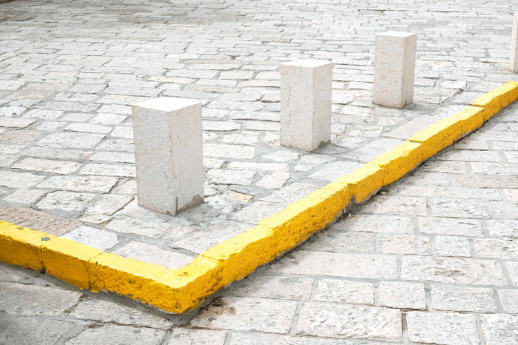 In A Row Traffic Architecture Block Block Shape Brick City Close-up Cobblestone Concrete Construction Industry Day Group High Angle View No People Outdoors Pavement Protection Side By Side Solid Stone Stone Material Street Wall Yellow