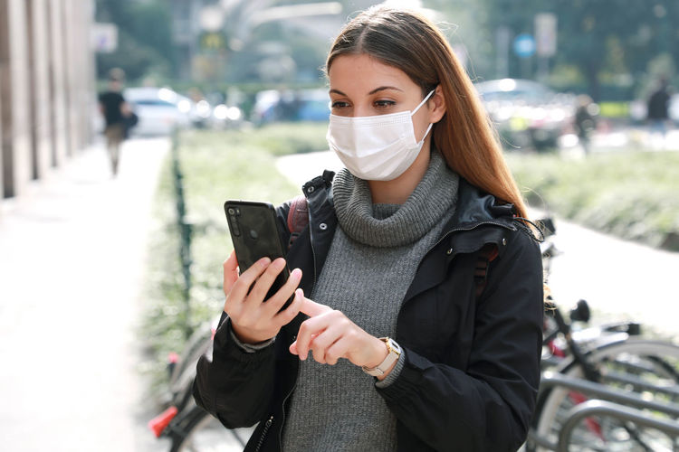 Young woman wearing mask using mobile phone while standing outdoors