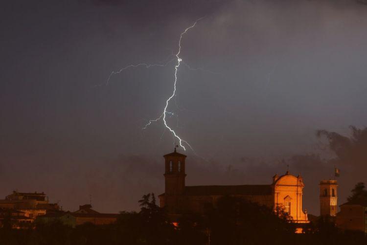 Lightning over illuminated buildings against sky at night