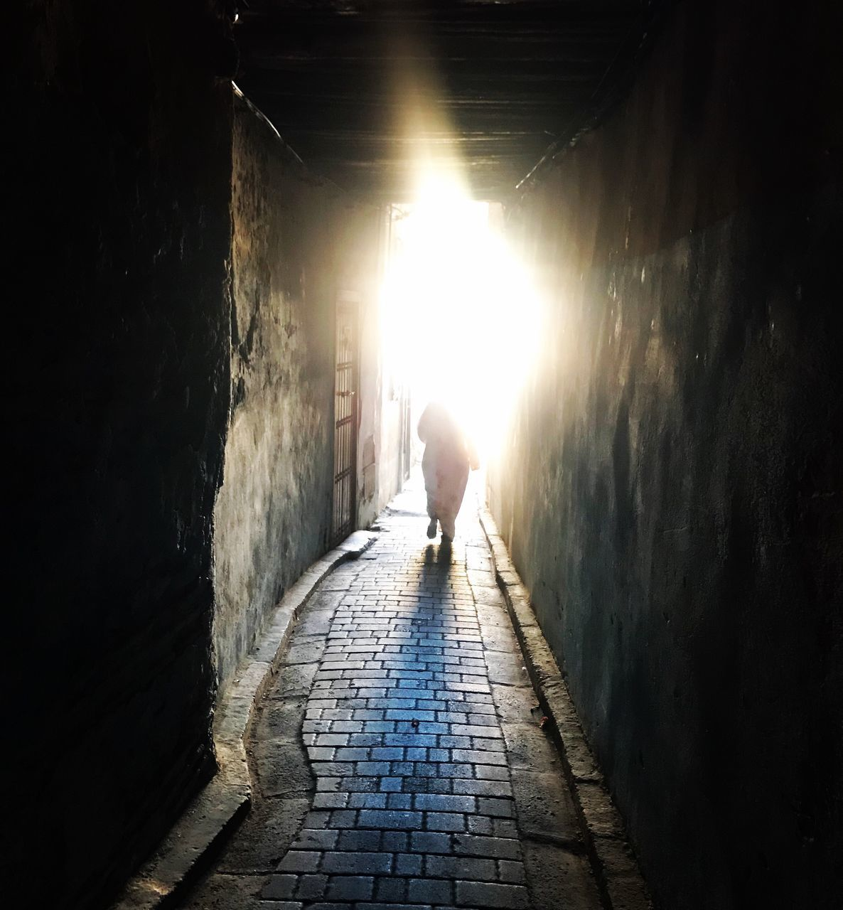 architecture, tunnel, the way forward, direction, one person, full length, wall - building feature, real people, built structure, lifestyles, light at the end of the tunnel, rear view, sunlight, men, walking, day, footpath, wall, leisure activity, outdoors, paving stone, alley, stone wall