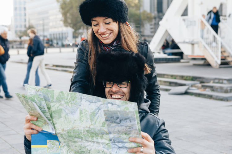 Cheerful friends looking at map in city