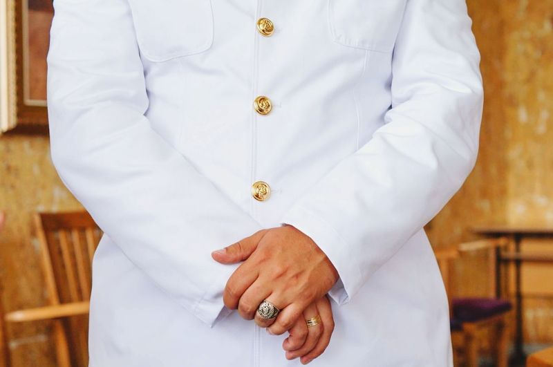 Midsection of man wearing white uniform