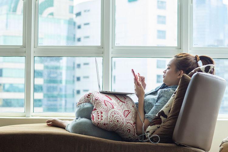 Side view of senior woman sitting on window