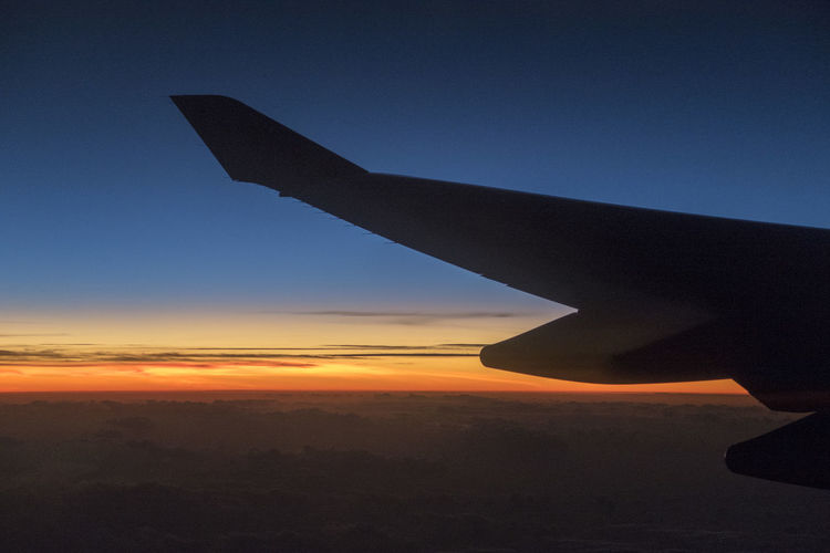 Silhouette airplane flying against sky during sunset