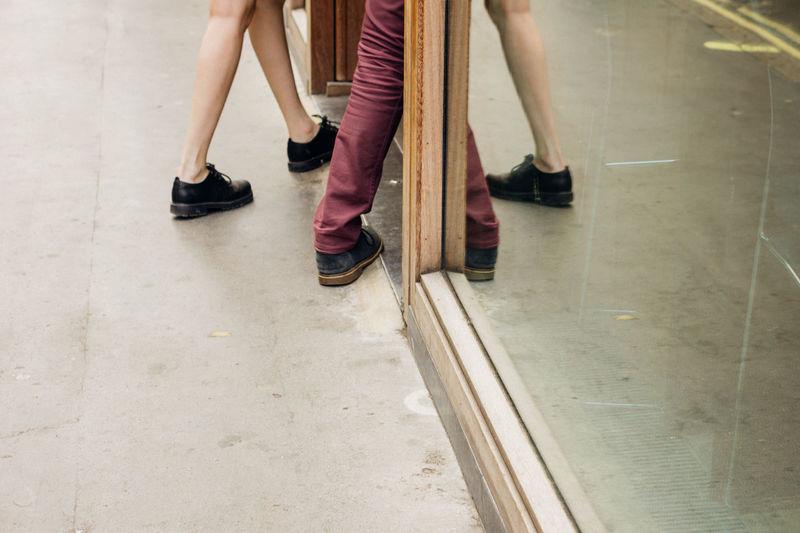 Low Section Of Friends Walking By Glass Window