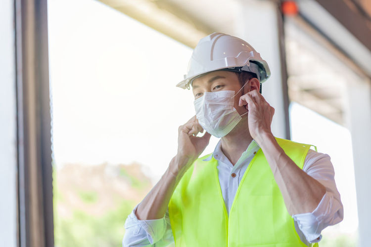 Worker wearing hardhat and mask
