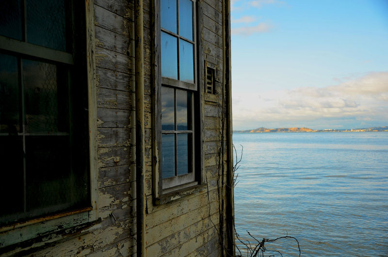 Abandoned building by river against sky