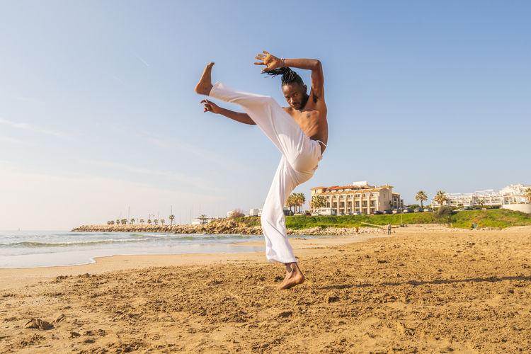 Man practicing capoeira at beach