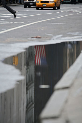 UPhold the flag American Flag City City Life City Street Day Diminishing Perspective Empty Focus On Foreground No People Nyc Street Life NYC Street Sce Outdoors American Dream Road Selective Focus Stationary Surface Level The Way Forward Vanishing Point Water Downfall.of The USA Reflection Reflections Reflection_collection Reflections In The Water Stories From The City