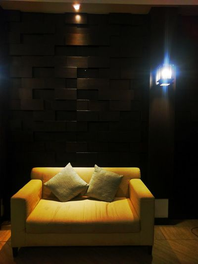 Illuminated lamps on sofa at home