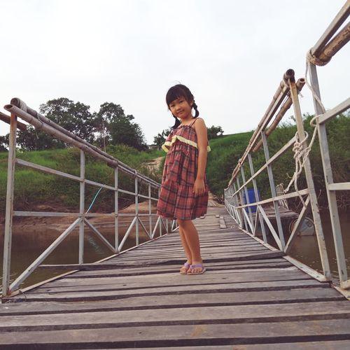 Portrait of girl standing on footbridge against clear sky