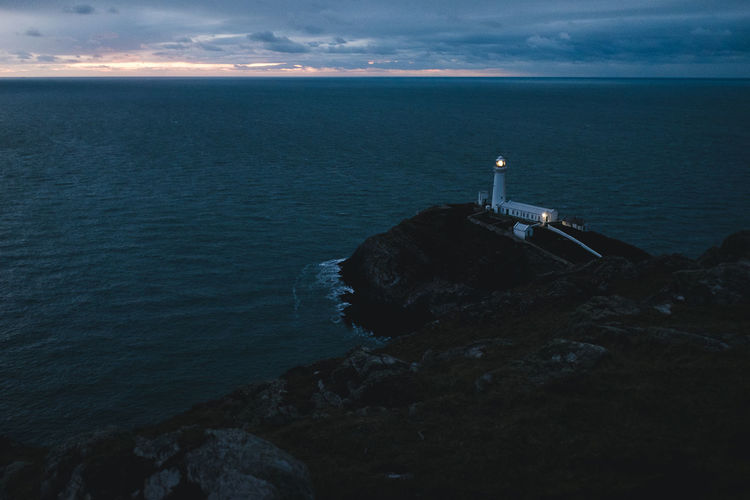 High Angle View Of Illuminated Lighthouse By Sea Against Cloudy Sky During Sunset