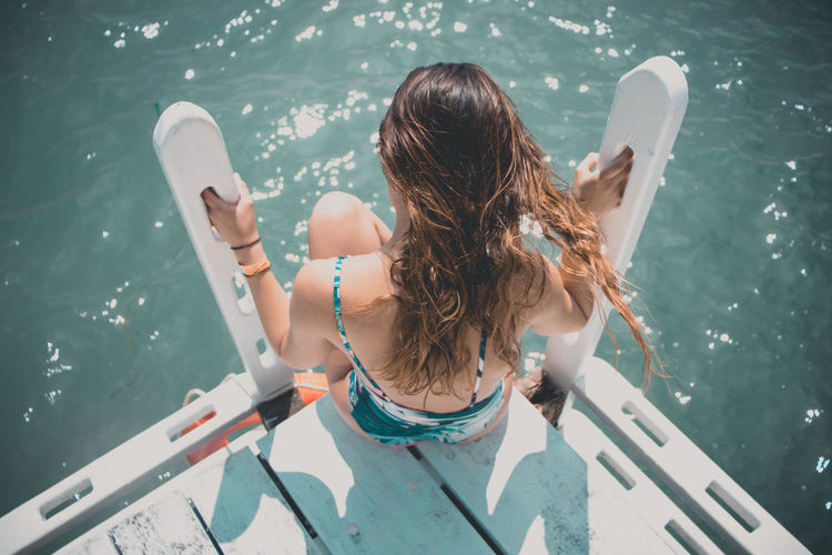 Rear view of woman sitting on boat in sea