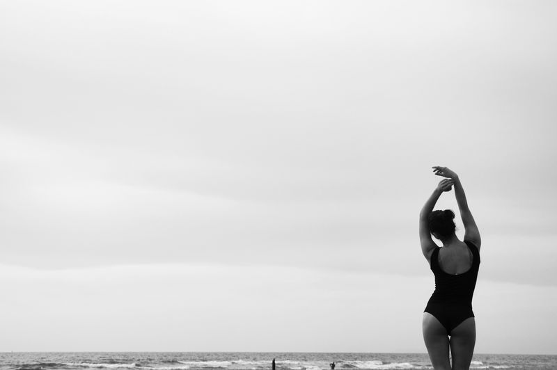 Rear view of young woman in swimsuit standing at beach against cloudy sky