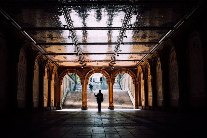 Silhouette man walking under arched ceiling