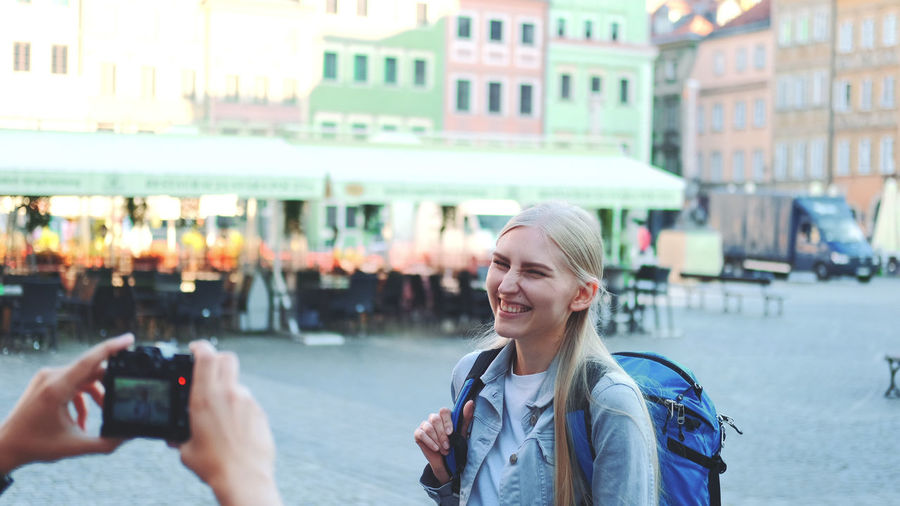 Portrait of smiling young woman using phone in city
