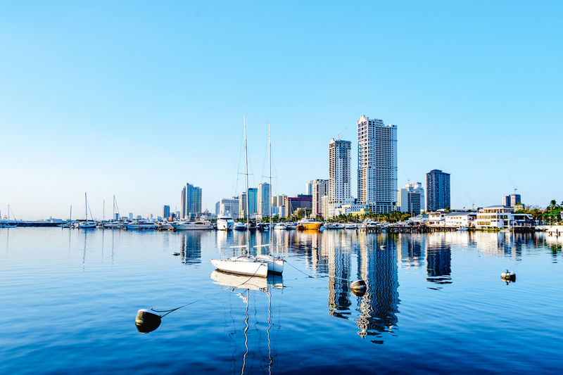 Sailboats in sea against modern buildings in city against clear blue sky