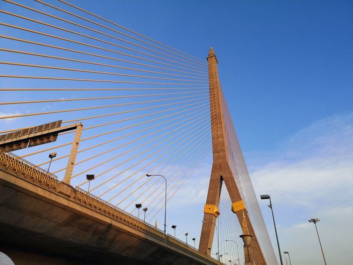 Low angle view of bridge and buildings against blue sky
