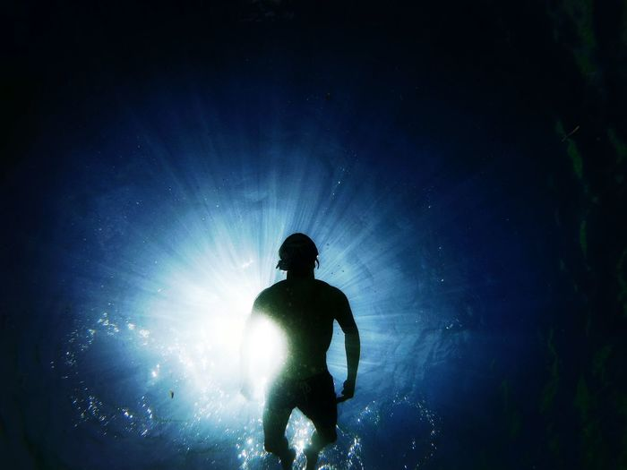 Low angle view of silhouette man swimming in sea