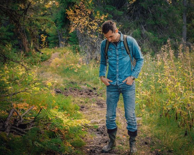 hiker thinking Hiker Tree Full Length Standing Forest Jeans Grass Casual Clothing Plant Life Hiker Denim Jacket Flower Head Petal Denim In Bloom Growth Children Blooming Countryside Casual Plant Pollen Growing