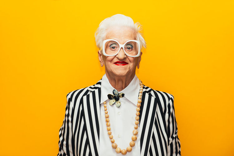 Portrait of stylish senior woman standing against yellow background