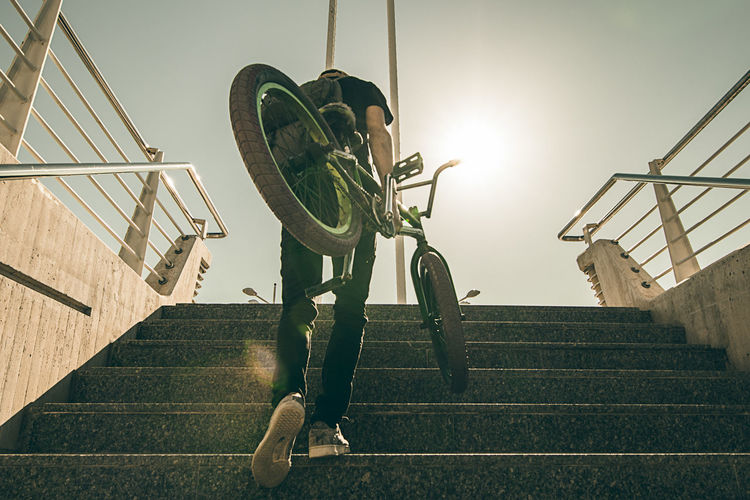 Low angle view of man on staircase against sky