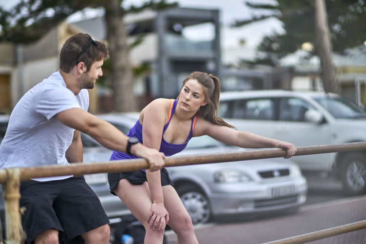 Young Woman Exercising With Fitness Instructor In City