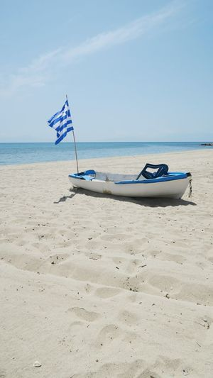 old broken fishing boat at the beach of nea plagia, greece Boat Fishing Greece Flag Hot Day Sun Copy Space Water Nautical Vessel Sea Beach Sand Blue Wave Sky Horizon Over Water National Flag Fluttering Flag Pole Seascape