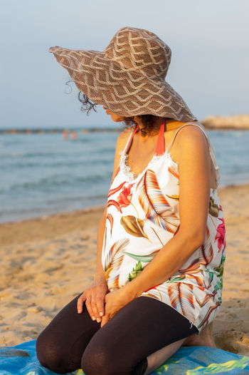 Midsection of woman sitting on beach
