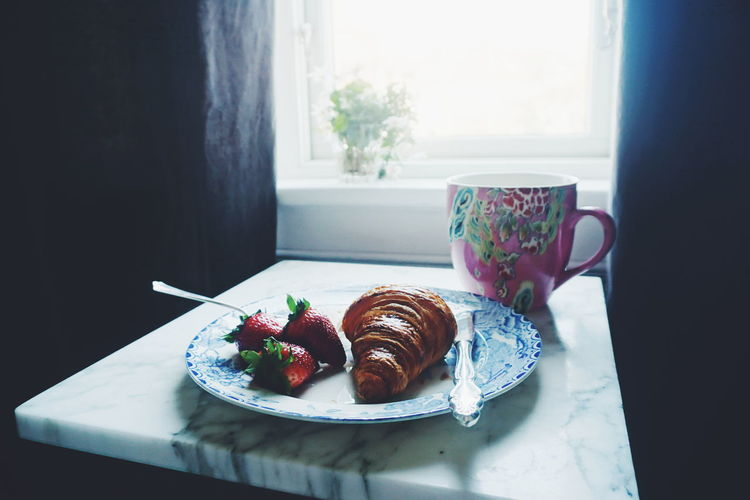 Croissant with strawberries in plate by cup on table