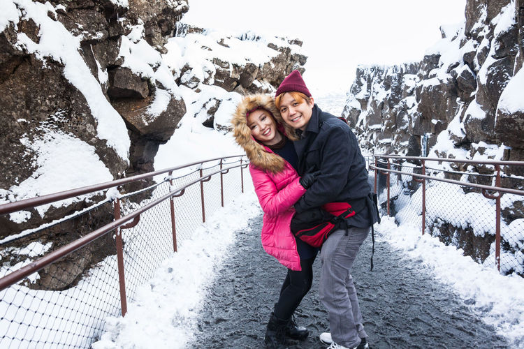 Portrait of smiling couple embracing while standing on road amidst mountain