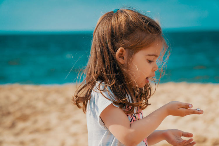 Summer Child Girl Kid Sea Beach Water Sky Childhood One Person Girls Land Women Leisure Activity Focus On Foreground Hairstyle Real People Innocence Females Brown Hair Lifestyles Casual Clothing Hair Outdoors