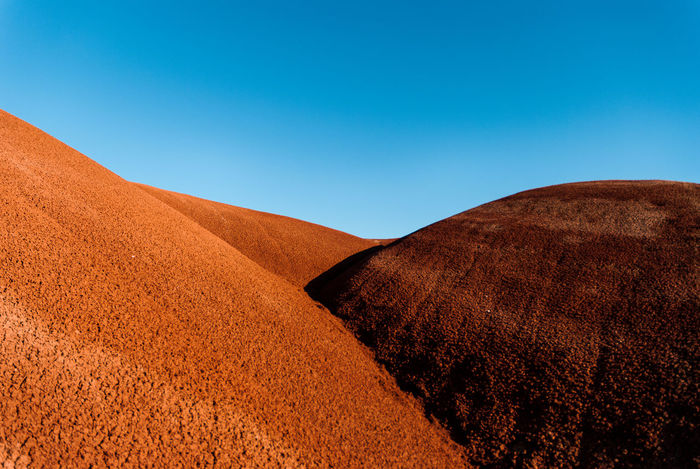 Scenic view of desert against clear blue sky