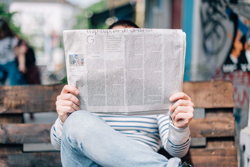 Hey guys! Just a short question: How do you prefer to get your news, internet or newspaper? On the go or with comfort? Book Casual Clothing Close-up Day Focus On Foreground Holding Human Hand Men Newspaper One Person Outdoors People Real People Text Women