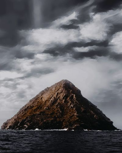 Rock formation in sea against cloudy sky