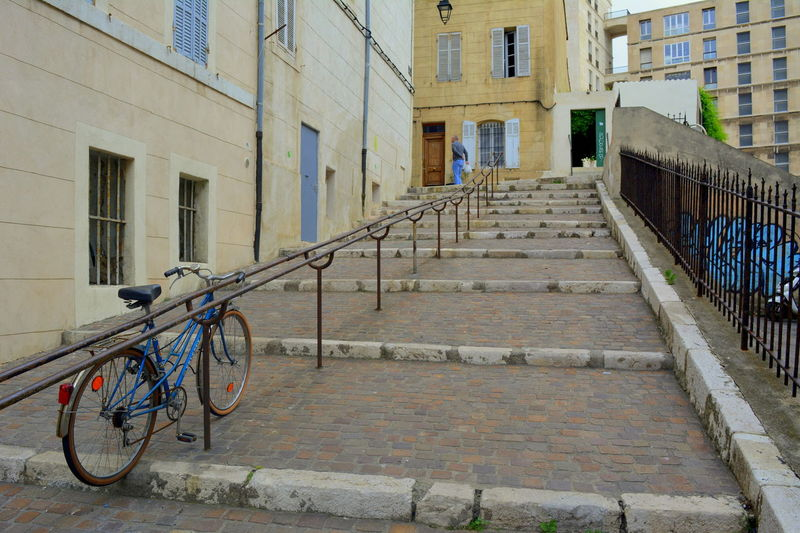 Bicycle on footpath amidst buildings in city
