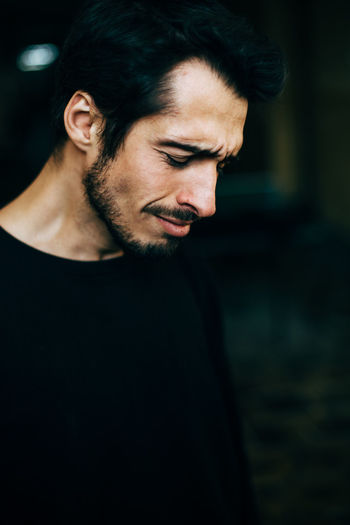 Sad young man wearing black t-shirt while crying