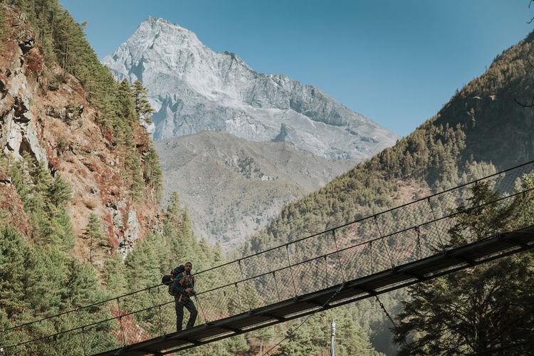 People walking on footbridge against mountains