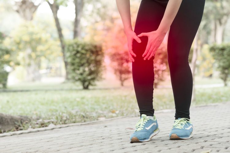 Low Section Of Woman With Knee Pain Standing On Footpath