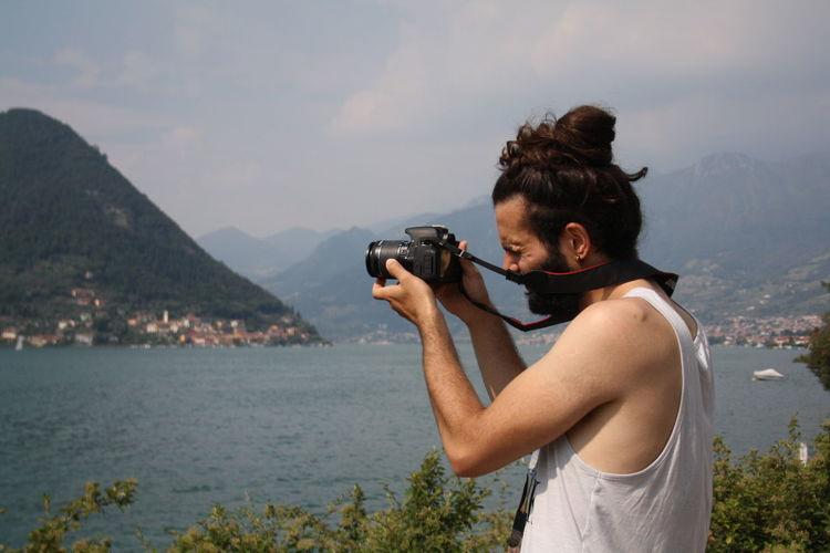 Man photographing through camera by lake against sky
