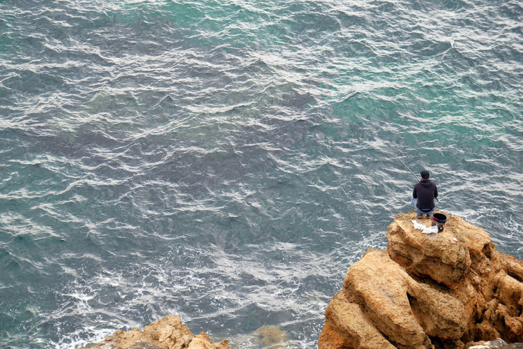 High angle view of man fishing while sitting on rock by sea