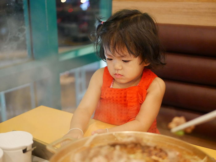 Girl looking away while sitting in restaurant