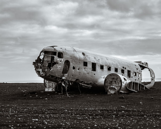 The wreckage of a crash landed transport plane on the black sand beaches of iceland.