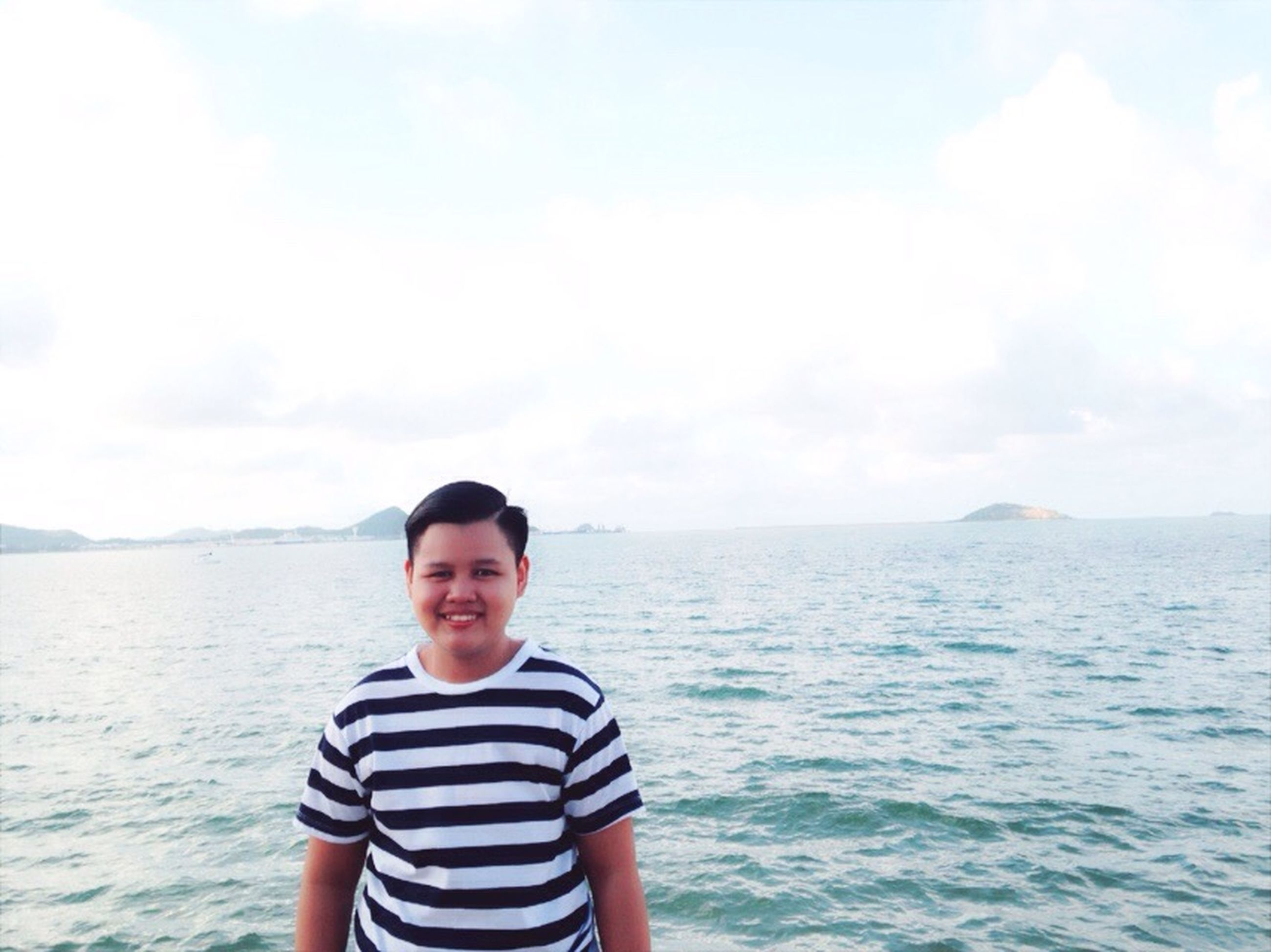 water, person, lifestyles, sea, leisure activity, sky, looking at camera, standing, waist up, portrait, casual clothing, young adult, young men, three quarter length, smiling, front view, nature, headshot