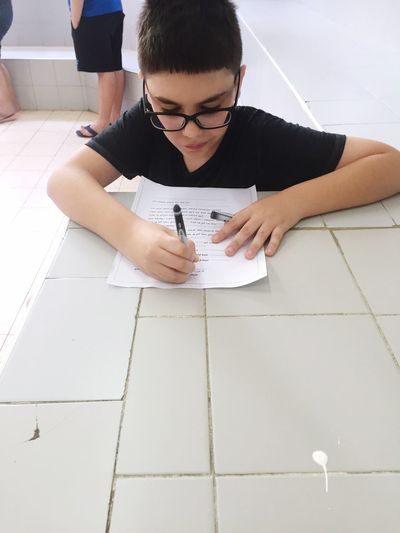 High Angle View Of Boy Writing On Paper In School