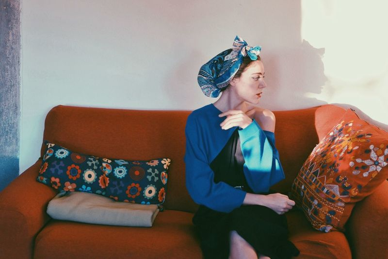 Woman wearing headscarf while sitting on couch at home