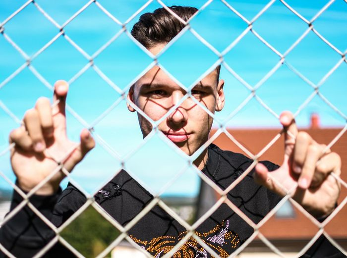 Portrait of man holding chainlink fence