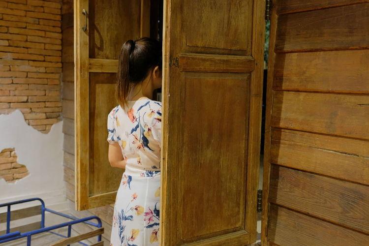 Rear view of woman standing at door